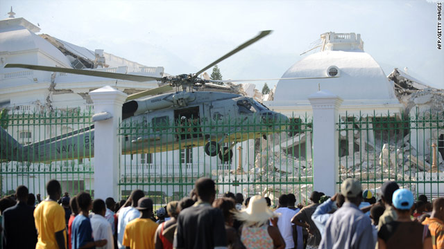 A crowd watches a U.S. Army helicopter land Tuesday on the grounds of Haiti's ruined Presidential Palace.