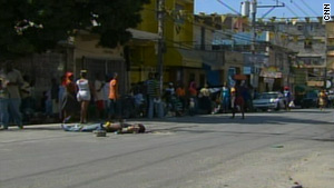 People walk by a gruesome scene Friday -- a man facing up, with arms out -- on John Brown Avenue after a mob left.