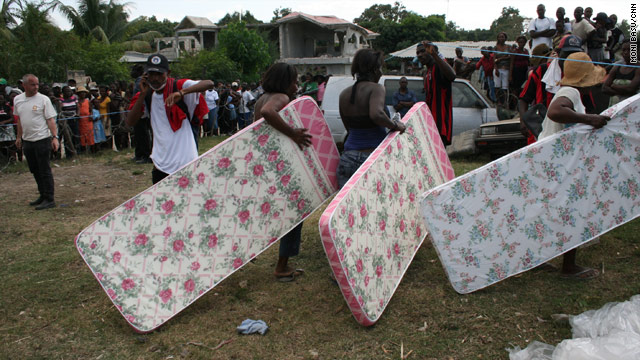 Quake victims receive mattresses from CARE International at a displaced people's settlement outside Leogane.