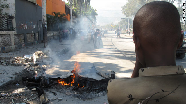 Three bodies burn Monday in a quake-crushed taxi in Port-au-Prince's Champs de Mars plaza.