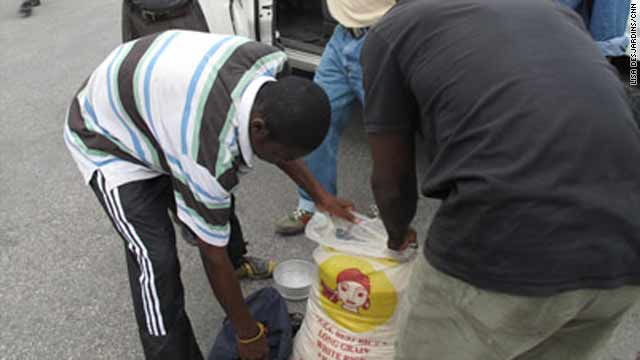People collect aid in the form of rice at the presidential palace on Monday in Port-au-Prince, Haiti.