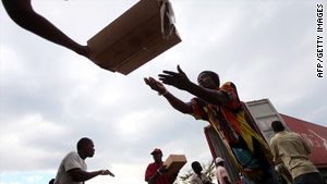 Workers unload food in a German government distribution program to help those displaced in earthquake in Haiti.