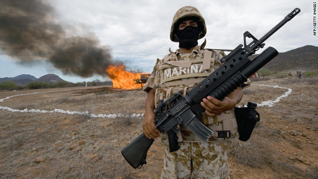 A Mexican marine stands guard as 7,000 kilograms of seized marijuana are incinerated on July 9, 2009, at the naval base in Guaymas, Sonora state, Mexico.