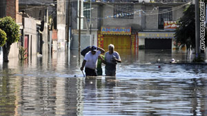 People wade through the flooded Valle de Chalco, on the outskirts of the Mexico City area, on Friday.