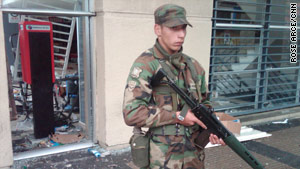 A soldier guards a looted mall on a main street in Concepcion, Chile, on Monday.