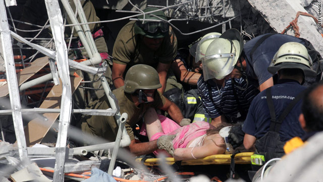 Rescue workers help an injured woman in Concepcion, south of Santiago, after Chile's 8.8-magnitude earthquake.