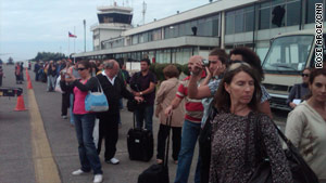Chileans line up Tuesday at the airport in Concepcion, Chile. The city is a scene of chaos and frustration.