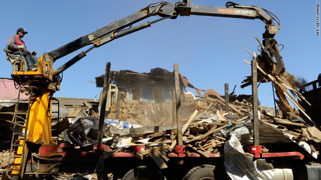 Crews remove rubble Thursday from a house destroyed in last week's earthquake in Constitucion, Chile.
