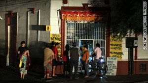 People in Santiago, Chile, gather outside a store after a power outage hit most of the country Sunday.