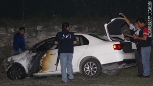 Mexican Federal Investigation Agency members inspect a car on a Nuevo Leon road blocked by drug suspects Thursday.