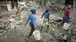 Women walk through a garbage-filled ravine in quake-Petionville, Haiti, on Wednesday.