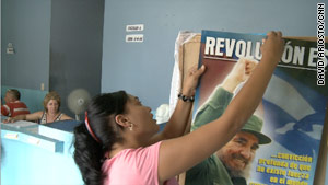 An election worker hangs a poster of former Cuban President Fidel Castro at a polling station in Havana, Cuba.