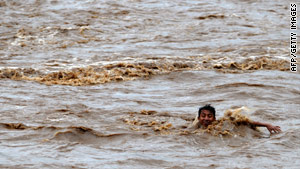 A boy tries to cross the overflowed Huiza River in La Libertad, south of San Salvador.