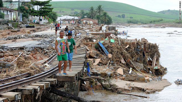 Local residents check damaged rail tracks next to the overflowing Mandau river in northeastern Brazil.