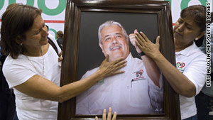 Supporters of slain candidate Rodolfo Torre Cantu touch his portrait during his funeral Tuesday in Ciudad Victoria, Mexico.