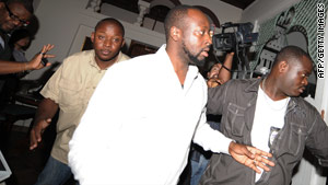 Wyclef Jean makes his way through a group of reporters on Friday in Port-au-Prince, Haiti