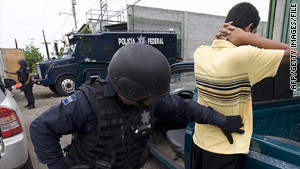 A Mexican federal police officer frisks a man during an anti-narcotics operation in Michoacan.