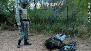 A Mexican soldier stands over one of the 25 drug suspects killed Thursday in a shootout in northeast Mexico.