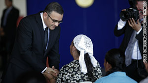 El Salvadoran President Mauricio Funes comforts relatives of  one of the 11 Salvadorans killed in the massacre.