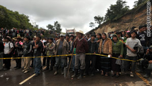 Relatives of missing people wait Sunday in Solola, west of Guatemala City, near the site of a recent landslide.