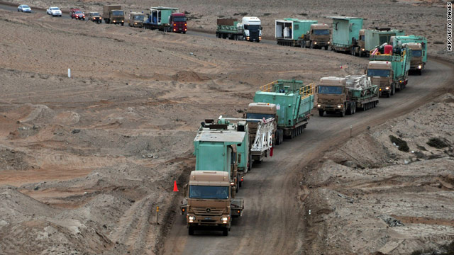Trucks carrying parts for a new drilling rig arrive Friday at a mine where 33 miners are trapped.