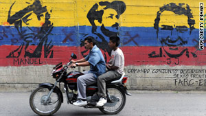 Motorcyclists ride past a mural showing dead FARC leaders in  El Palo, Colombia.