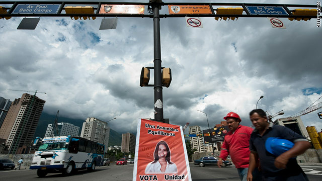 Two men pass by a poster of an opposition candidate to the national parliament in Caracas on September 24.