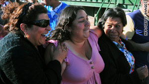 Relatives of one of the trapped miners react Tuesday upon hearing how far rescuers have drilled.
