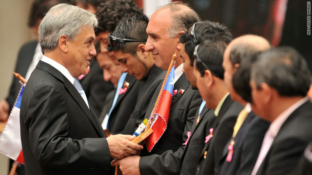 Chilean President Sebastian Pinera gives a gift to miner Jose Henriquez at a ceremony in Santiago on Monday.