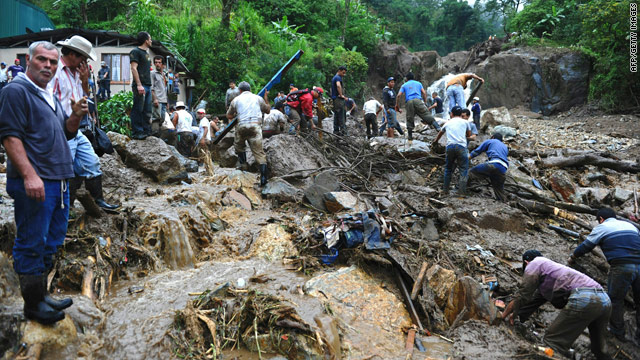 Inhabitants of San Antonio de Escazu and rescue personnel remove debris after a landslide hit the village early Thursday.