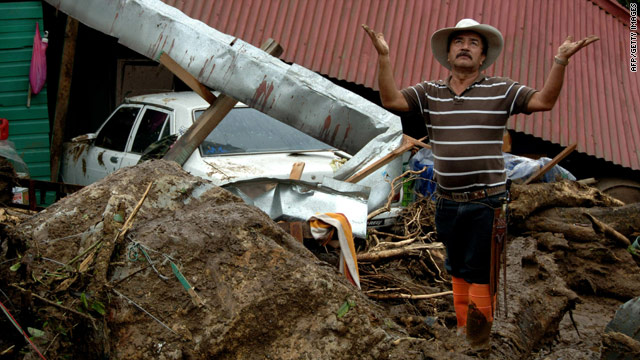 A man prays in front of a house destroyed by mudslides in San Antonio de Escazu, Costa Rica, on Thursday.