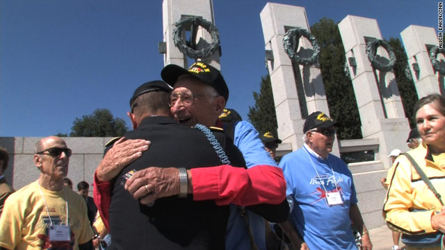 Veteran Dick Coss hugs an enlisted family member who surprised him at the World War II memorial.