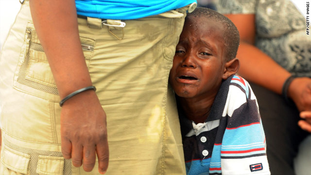 A mother comforts her boy, who is stricken with cholera, in the Cite Soleil slum of Port-au-Prince, Haiti.