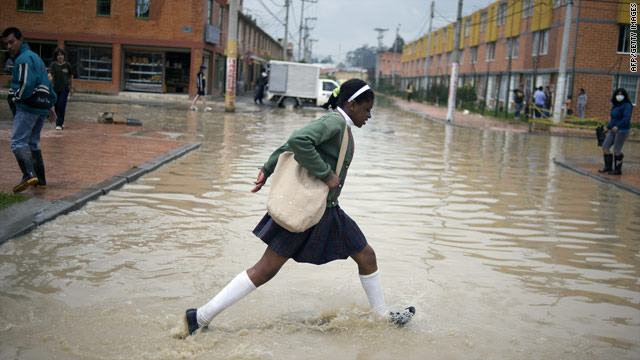 A girl crosses a flooded street in Bogota on Thursday during flooding that has affected 1.2 million people in Colombia