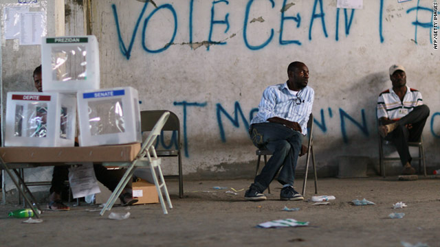 Poll workers sit idle next to ballot boxes after their polling station was closed down Sunday in Port-au-Prince, Haiti.