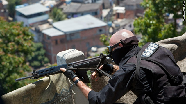A Coordination of Special Resources (CORE) policeman aims his gun in the Alemao slum of Rio de Janeiro on Monday.