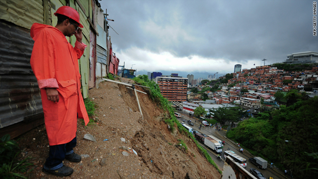 An employee of the municipality looks at the site of a landslide in Caracas, Venezuela's Roca Tarpeya neighborhood on Tuesday.