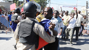 Police guard a recent demonstration in Port-au-Prince, when protesters took to the streets, seeking annulment of the vote.
