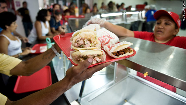 A customer buys food as others line up at an Arepera Socialista restaurant in Caracas, Venezuela.