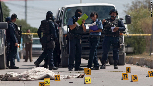 Mexican police agents look at a man's corpse on a street of Ciudad Juare on October 4, 2010.