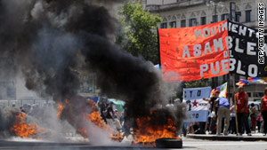 Protesters wave flags and burn tyres at 9 de Julio Avenue in Buenos Aires on December 20.