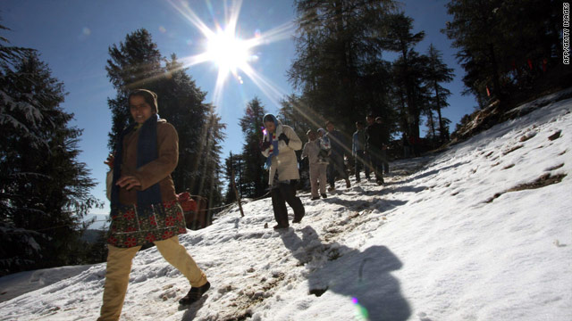 Tourists walk on fresh snow Monday near Shimla in Himachal Pradesh, northern India.