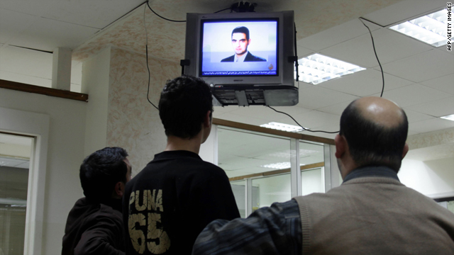 Employees look at a picture of Jordanian Humam Khalil Abu-Mulal al-Balawi broadcast by the Qatar-based Al-Jazeera satellite news channel at an office in the Jordanian capital Amman on January 6, 2010.
