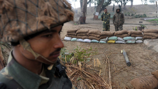 Indian soldiers stand guard near an unexploded rocket which India accused Pakistan of firing across the border.