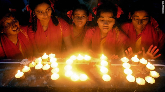 Bangladeshi acid attack victims use candles to write the word 'ACID' to mark International Women's Day