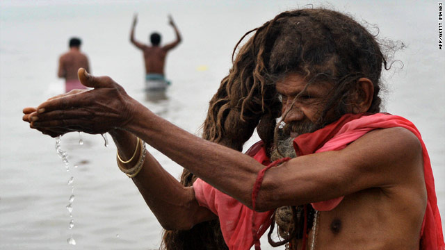 "A holy man offers water to the Sun God during the ""Gangasagar"" where the river Ganges connects with the Bay of Bengal."