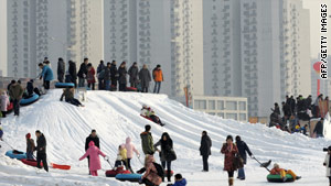 Tourists enjoy snow surfing at a resort by a high-rise apartment buildings in Beijing.
