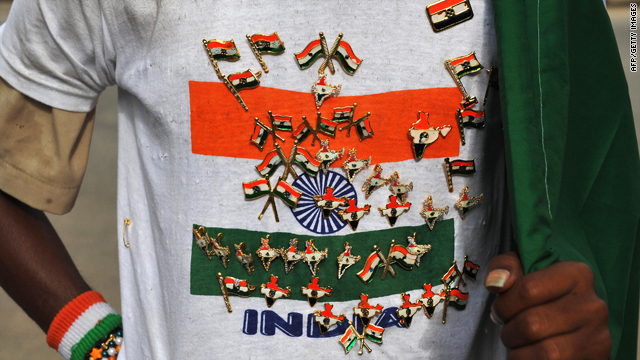 An Indian street vendor with badges pinned to his T-shirt sells Indian national flags to commuters on the eve of the country's Independence Day in Bangalore on August 14, 2009.