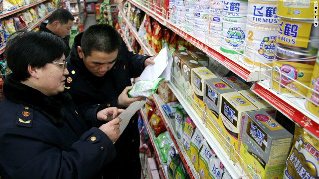 Health enforcement officers check labels on milk powders at a store in east China's Anhui province.