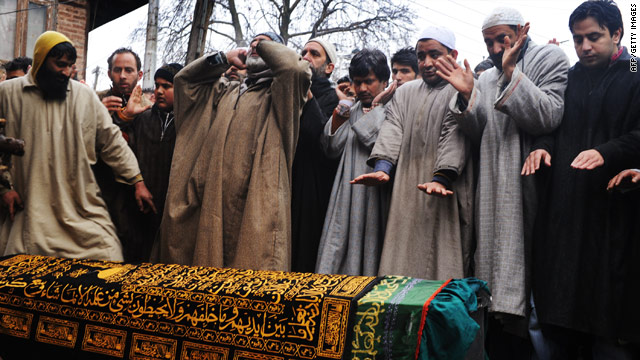 Men pray over the coffin of Zahid Farooq Sheikh at his funeral in Srinagar on February 6, 2010.